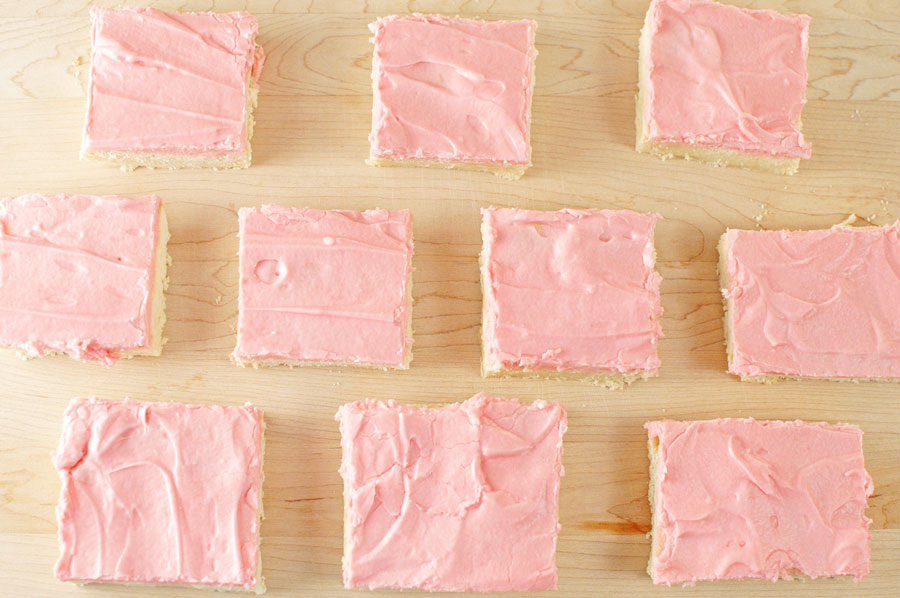 Sugar Cookies Bars dessert with pink frosting lined up on platter