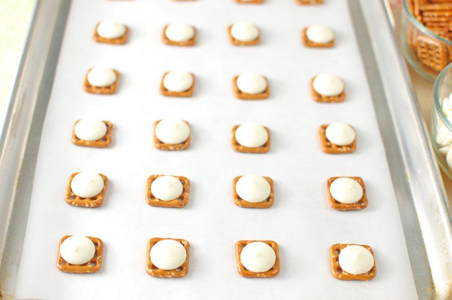 melting wafers on pretzel snaps for flower pretzel bites