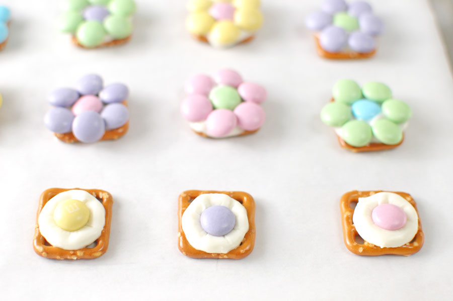 m&ms on top of melting wafer and pretzel snap for flower pretzel bite